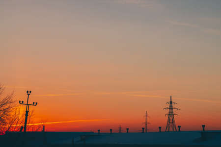 Power lines above roof on dawn. Silhouettes of tower with wires among smog on sunrise. High voltage cables on warm orange yellow sky. Power industry at sunset. City power supply. Mist urban background