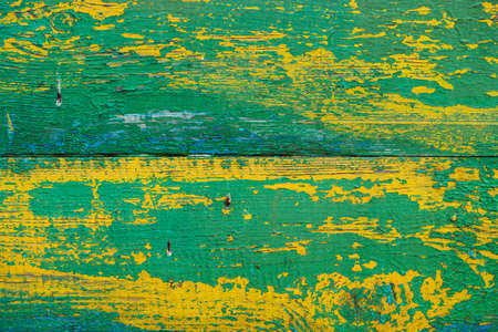 Old wooden painted rustic wall with yellow green flaky dye. Faded wood plank close-up. Peeling paint on board. Damaged rough wooden texture. Imperfect wood surface. Background with weathered paint.
