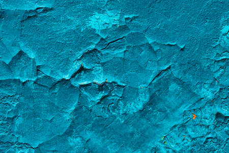 Imperfect concrete surface. Cracked blue paint close-up. Damage texture in macro. Grungy plaster. Old stucco textured background. Rough faded uneven obsolete wall. Peeling of old paint. Flaking of dye Banco de Imagens