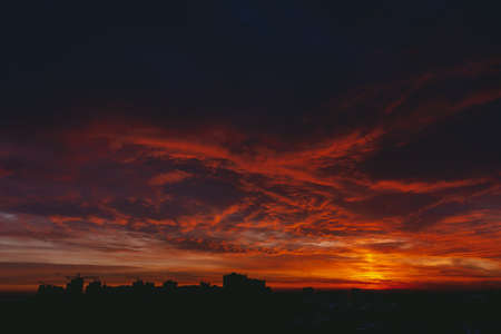 Fiery red blood vampire dawn. Amazing warm dramatic fire blue dark cloudy sky. Orange sunlight. Atmospheric background of sunrise in overcast weather. Hard cloudiness. Storm clouds warning. Copy space Stockfoto