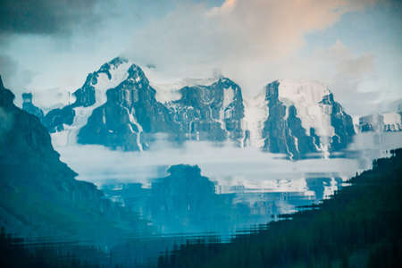 Huge glacier reflected in water surface. Water reflection of giant snowy rocky mountains under cloudy sky. Thick fog in mountains. Atmospheric landscape. Tranquil reflection in mountain lake. Banco de Imagens - 122474897