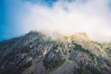 Giant cloud above rocky ridge with trees in sunlight. Amazing mountain range under blue cloudy dawn sky. Wonderful foggy rocks. Misty landscape of highland nature. Low clouds in morning sunny light.