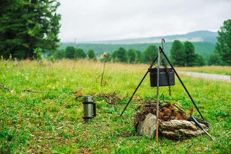 焚き火の上の三脚の大釜。自然に食べ物を調理する。屋外での夕食。薪、枝、ブラシウッドが燃えている。アクティブな休息。山でのキャンプ。