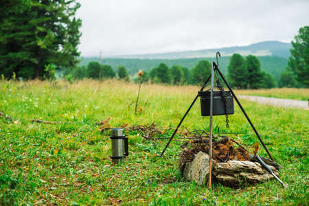 Cauldron on tripod above bonfire. Cooking of food on nature. Dinner outdoors. Firewood, branches and brushwood in fire. Active rest. Camping in mountains. Stockfoto