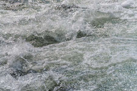 Natural texture of foamed water surface. Rapids of river close-up. Fast flow in mountain creek. Background of clean water waves with copy space. Textured foam of shiny stream. Fast river texture.