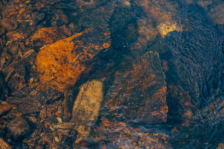 Underwater smooth stones in spring water close-up. Clean water flow among red stones. Colorful natural background of mountain spring stream with copy space. Beautiful texture of creek bottom.