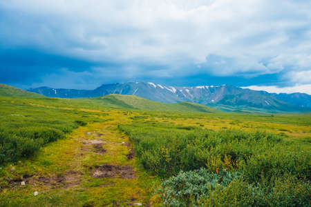 Spectacular view of distant giant mountains. Footpath through valley in highlands. Hiking path. Wonderful huge mountain range under cloudy sky. Amazing dramatic green landscape of majestic nature. 版權商用圖片 - 122479097