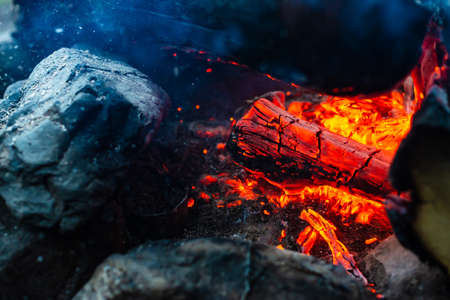 Smoldered logs burned in vivid fire close up. Atmospheric background with orange flame of campfire. Unimaginable detailed image of bonfire from inside with copy space. Smoke and glowing embers in air. Stockfoto