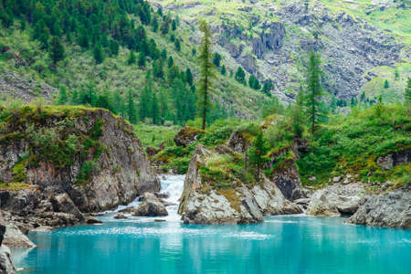 Mountain creek flows into azure lake. Fast stream of brook. Smooth water surface. Wonderful rocks with rich vegetation of highlands. Beautiful conifer trees. Amazing landscape of majestic nature.