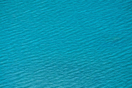 Amazing textured background of calm azure clean water surface. Sunshine in mountain lake close up. Beautiful ripples on shiny water in sunny day. Wonderful relax texture. Imagens