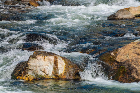 Big boulders in mountain creek close-up. Rapids of fast river with copy space. Foamed water stream. Fast flow near wet stones. Background of clean water waves. Natural texture of shiny stream of creek