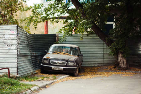 Volga GAZ 3110. Beautiful russian black car parked under tree near metallic fence in autumn. Fall yellowed leaves on hood. Atmospheric urban landscape. Dirty sedan. Barnaul, Russia, 30 Sep, 2016. Éditoriale