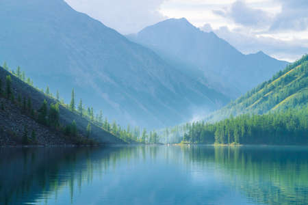 Gespenstischer Bergsee im Hochland am frühen Morgen. Schöne neblige Berge, die sich in der ruhigen klaren Wasseroberfläche widerspiegeln. Rauch von Lagerfeuern. Erstaunliche atmosphärische Nebellandschaft von majestätischer Natur.