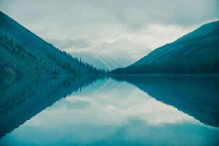 Incredibili sagome di montagne e nuvole basse riflesse sul lago di montagna. Belle increspature sullo specchio d'acqua. Cielo nuvoloso negli altopiani. Atmosferica paesaggio spettrale. Meraviglioso paesaggio mistico di montagna.