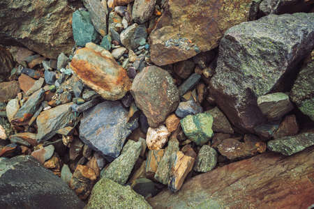 Multicolored boulder stream. Loose rock close up. Randomly scattered stones in nature. Amazing detailed background of highlands boulders with mosses and lichens. Natural texture of mountain terrain.