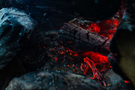 Smoldered logs burned in vivid fire. Atmospheric background with orange flame of campfire. Unimaginable detailed image of bonfire from inside with copy space. Smoke and ashes close up.