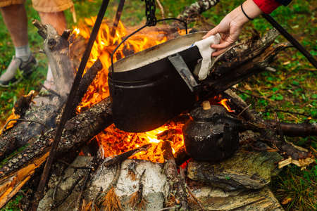 People cook food in open air. Cauldron on tripod above bonfire. Dinner outdoors. Firewood, branches and brushwood in fire. Active rest. Camping. Atmospheric fire.
