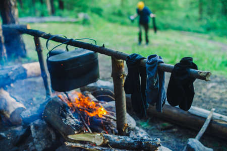 Drying wet clothing on the bonfire during camping. Socks drying on fire. Cauldron and kettle above campfire. Cooking of food on nature. Firewood and branches in fire. Active rest in forest. 写真素材