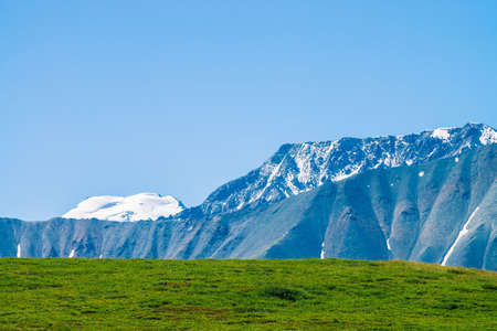 Giant mountains with snow above green valley in sunny day. Glacier under blue sky. Meadow with rich vegetation of highlands in sunlight. Amazing snowy mountain landscape of majestic nature. 写真素材