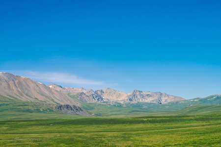 Giant mountains with snow above green valley under clear blue sky. Meadow with rich vegetation of highlands in sunlight. Amazing sunny mountain landscape of majestic nature. 写真素材