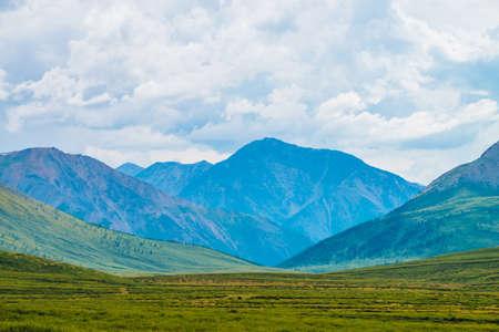 Spektakuläre Aussicht auf riesige Berge unter bewölktem Himmel. Riesige Bergkette bei bedecktem Wetter. Wunderbare wilde Landschaft. Atmosphärische dramatische Hochlandlandschaft von majestätischer Natur. Malerische Bergwelt. Standard-Bild