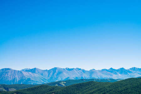 Giant mountains and glaciers above hills with forest. Snowy ridge under blue clear sky. Snow summit in highlands. Permafrost, permanent cold. Amazing atmospheric minimalist mountain landscape. 写真素材