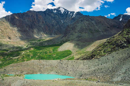 Turquoise water of mountain lake near huge rocky mountain range with snow. Huge clouds in blue sky above amazing snowy mountains. Wonderful atmospheric landscape of majestic nature of highlands. 写真素材