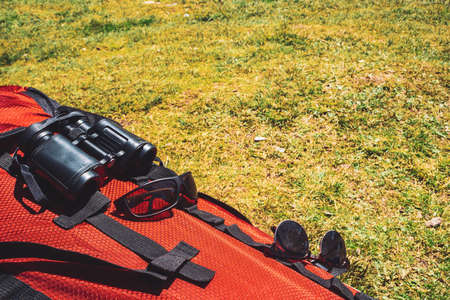 Big red camping backpack with traveler items (sunglasses, binocular) on grass in sunny day. Active rest. Hiking on nature. Mountain trekking. Amazing leisure activity in highlands.