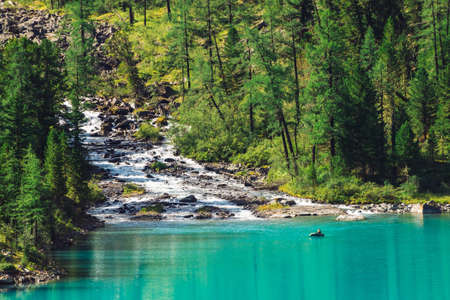 Mountain creek flows into lake. View above fisherman in boat on azure water. Wonderful forest in sunlight. Big boulders in brook. Atmospheric beautiful landscape of highland nature in sunny day.