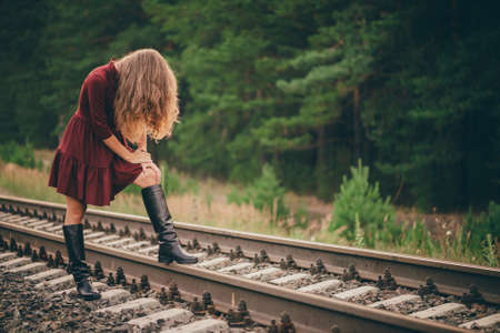 Beautiful sad girl is hiding face by hair. Moody lady in burgundy dress in forest on railway. Depressed lonely girl on railroad at dawn. Sun in curly natural hair in autumn. Bad mood. Offended girl.