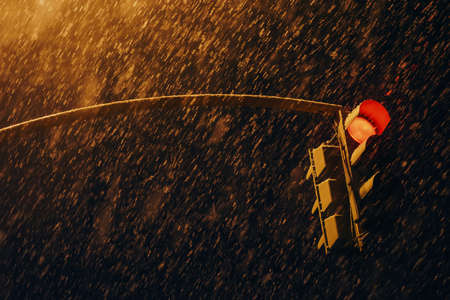 Red traffic signal in dark time close up. Traffic light at strong snowfall. Huge snowflakes above road. Stop signal in night. Atmospheric background with copy space. Traffic Laws. No traffic. 写真素材