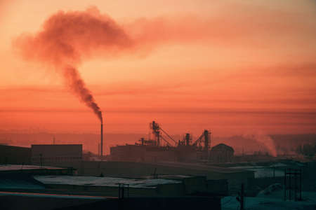 Smoke from pipe pollutes environment in dawn. Storage of goods in warehouses in winter. View from above of industrial area in sunrise in pink tones. Industrial buildings zone close up with copy space.