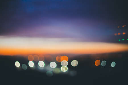 Wonderful atmospheric calm dawn above city. Amazing picturesque romantic sunset. City lights in bokeh. Cozy abstract blurred background of scenic sunrise. Tranquil scenery. Vintage landscape. 写真素材