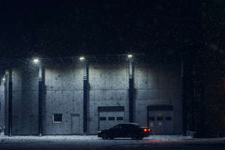 Black car parked near office building in winter evening in strong snow storm. Automobile near auto service in night. Machine near automatic gate for maintenance. Modern architecture in dark night.