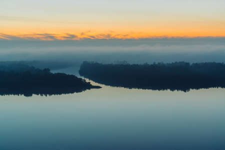 Broad river flows along shore with forest under thick fog. Early blue sky reflected in water. Yellow glow in picturesque predawn sky. Colorful morning mystical atmospheric landscape of majestic nature
