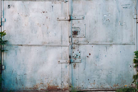 Closed imperfect rust metallic garage gate close-up. Damage texture of locked rusty iron door. Grungy metal surface. Textured background of rough faded uneven steel gates. Obsolete metal surface. 版權商用圖片