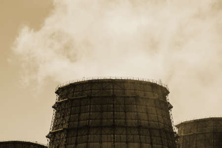 Three big tower of CHPP close-up. Steam from wide pipe of CHP on sky. Industrial background of TPP in sepia tones with copy space. Huge pipes of thermal power plant produce steam for electric power. 版權商用圖片