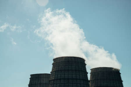 Three big tower of CHPP close-up. White steam from wide pipe of CHP on blue sky. Industrial background image of TPP with copy space. Huge pipes of thermal power plant produce steam for electric power. 版權商用圖片