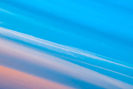 Varicolored striped surreal sky with shades of blue, cyan, cobalt, pink colors. Diagonal lines of smooth clouds. Atmospheric background image of tender sky. Фото со стока