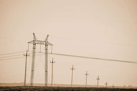 Atmospheric landscape with power lines in field under sky in sepia tones. Background image of electric tower with copy space. Wires of high voltage above ground. Electricity industry in monochrome.