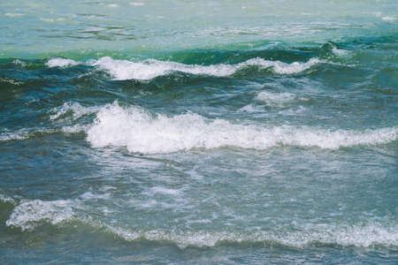 Detailed texture of turquoise rushing water surface. Rapids of mountain river close up. Background of clean water waves.