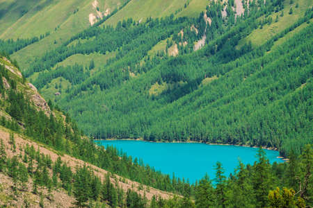 Wonderful mountain lake in valley of highlands. Smooth clean azure water surface. Giant mountainside with rich vegetation. Amazing coniferous forest. Atmospheric green landscape of majestic nature. Standard-Bild - 124054107
