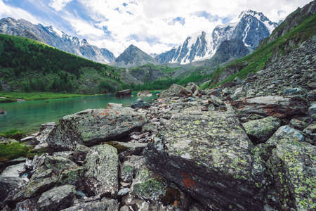 Mountain lake is surrounded by large stones and boulders on front of giant beautiful glacier. Amazing mountain in shape of pyramid. Snowy ridge under cloudy sky. Wonderful atmospheric landscape. Standard-Bild - 124054112