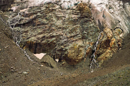 Foothills of giant glacier. Amazing rocky relief with snow and ice. Wonderful huge mountain rocky natural wall with small waterfalls. Water from glacier. Fantastic artwork of majestic highland nature. Standard-Bild - 124054111