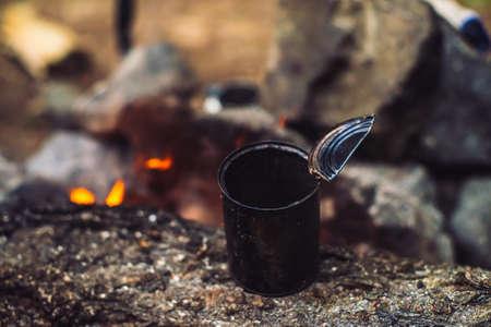 Heating of tea in metal mug on bonfire with large firewood. Tea drinking in open air. Active outdoor recreation. Camping in dusk. Romantic warm atmosphere in twilight on nature. Active rest. Standard-Bild - 124054179