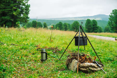 Cauldron on tripod above bonfire. Cooking of food on nature. Dinner outdoors. Firewood, branches and brushwood in fire. Active rest. Camping in mountains. Standard-Bild - 124054186