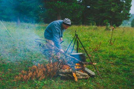 Tourist kindles fire. Traveler is lighting fire in camp. Man puts dry branch in campfire. Active outdoor recreation. Into the wild. Camping in dusk. Atmospheric warm in twilight. Active rest. Standard-Bild - 124054260