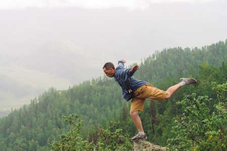 Mad tourist on mountain peak. Joyful traveler stands on one leg over abyss. Crazy man is jumping on rocky summit. Positive person in flight over precipice. Exciting rainy moment. Freedom in highlands. Standard-Bild - 124054273