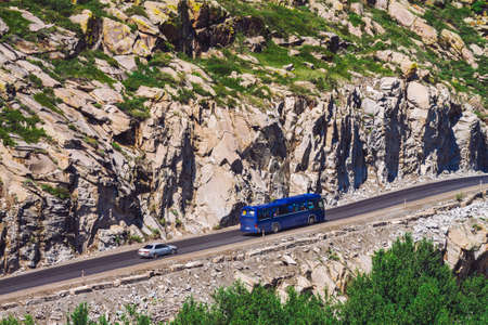 Ð¡ar drives along highland highway over abyss near giant rocky cliff. Amazing highlands road on pass. Tourists in bus. Trip in mountains. Mountain tourism. Standard-Bild - 124054264