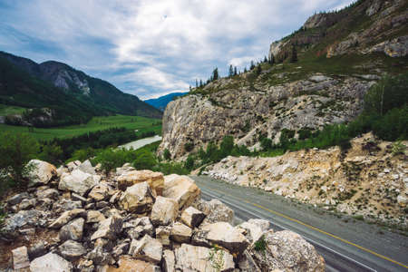 Highway across pass in mountains. Asphalt road near rocky cliff. Mountain river in valley. Amazing colorful highland landscape of majestic nature. Standard-Bild - 124054267